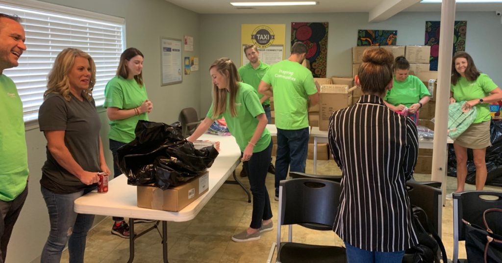 Hundreds of backpacks are being filled by the team from Insperity with supplies so they are ready to provide to children at their Well Check Exams